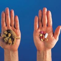 Two Hands one with herbs and one with Pharmaceutical drugs